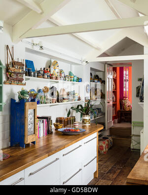 Open shelving with assorted crockery in kitcehn with wooden work tops and white pitched ceiling - Stock Photo