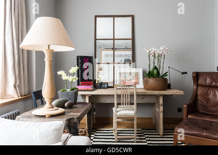 Wood pot of orchids on rustic wooden table in sitting room with panelled mirror and wing back leather armchair - Stock Photo