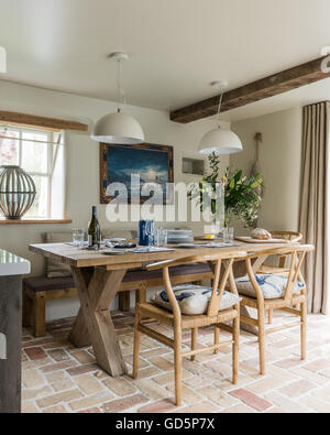 Antique oak dining chairs around rustic wooden table in kitchen with terracotta floor tiles and wooden ceiling beam - Stock Photo