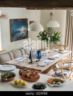 Seafood feast laid out on worktop by laid dining table - Stock Photo