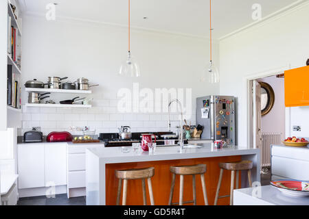 Wooden bar stools in high ceilinged kitchen with white metro tiles. The clear glass dome lights are from Baileys - Stock Photo