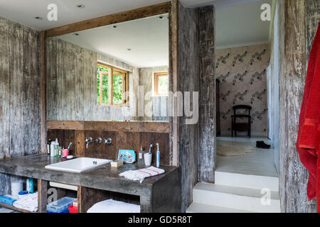 Polished concrete vanity unit in ensuite bathroom with walls lined with recycled floorboards - Stock Photo