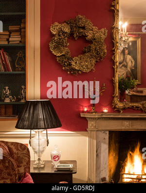 Black lamp on wooden side table with lit fire in Surrey Rectory, England, UK - Stock Photo