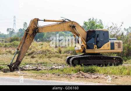 Dirty excavator vehicle on the construction site near the urban park,Thailand. - Stock Photo