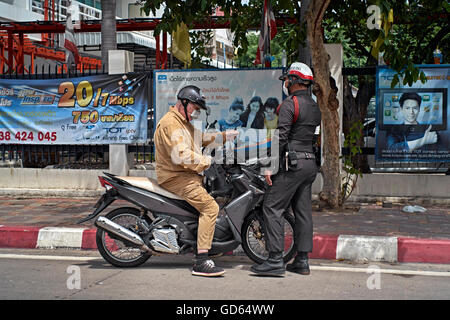 Motorcyclist stopped by Thai police officer for traffic violation. Thailand S. E. Asia - Stock Photo