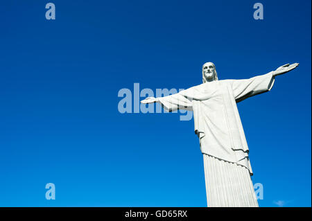 RIO DE JANEIRO - MARCH 05, 2016: Statue of Christ the Redeemer stands in clear blue sky in bright morning sun. - Stock Photo