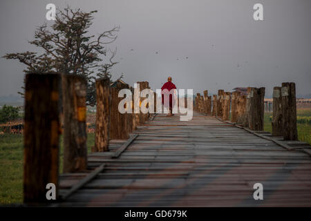A Buddhist monk walks along the U Bein bridge at sunrise, Amarapura, Myanmar. - Stock Photo