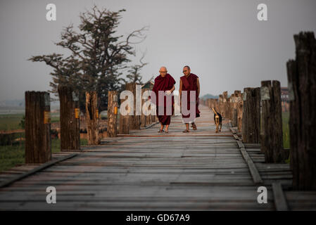 Two Buddhist monks walk along the U Bein bridge at sunrise, Amarapura, Myanmar. - Stock Photo