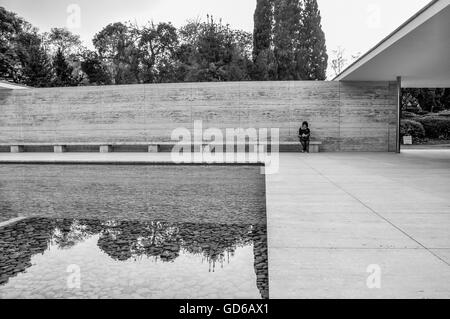 Single person sitting on bench at Barcelona Pavilion with calm reflecting pool in foreground - Stock Photo
