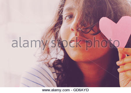 Young woman holding pink heart sign - Stock Photo