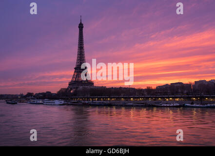 Fiery sunrise on the Eiffel Tower and Seine River with Port de Suffren, Paris (7th and 15th arrondissements) - Stock Photo