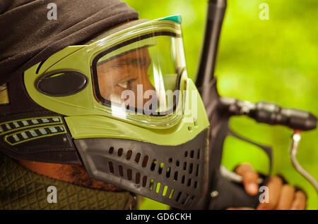 Closeup headshot man wearing green and black protection facial mask standing in profile angle, forest background, - Stock Photo