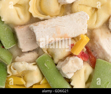 Top close view of a frozen TV dinner of chicken, tortellini and assorted vegetables. - Stock Photo