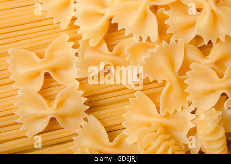 Raw pasta background.  Mixed dried pasta selection on black wooden background. Variety of types and shapes of Italian - Stock Photo