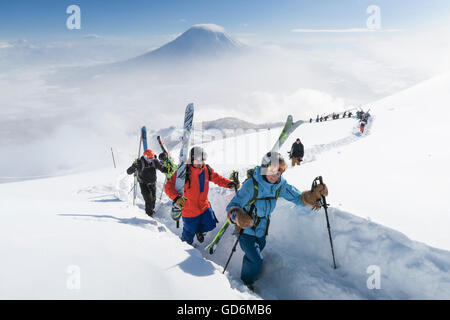 With Mount Yotei in the background, a team of backcountry skiers, led by a woman, are hiking to the summit of mount - Stock Photo