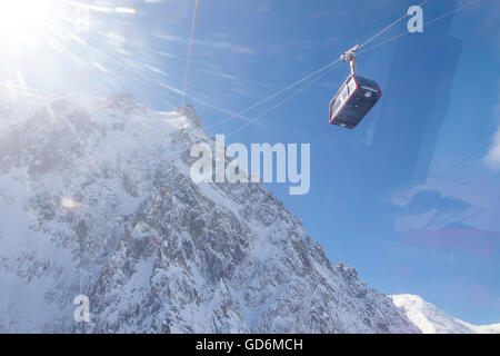 A cabin of the Aiguille du Midi cable car is entering the halfway station at Plan de l'Aiguille. The steep north - Stock Photo