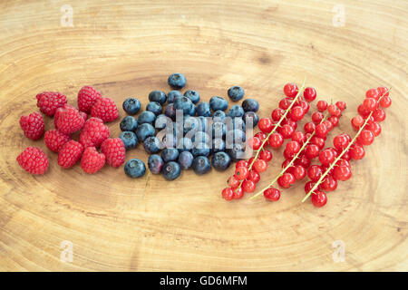 Group of raspberries, bilberries and red currants placed on a wooden board. - Stock Photo