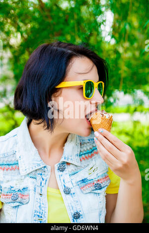 Young girl eating delicious ice cream in summer hot weather wearing yellow and blue clothes and sunglasses - Stock Photo