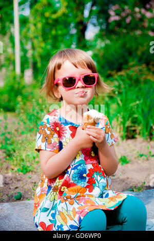 Cute and happy little girl in pink sunglasses sitting and eating ice cream outdoor. Yummy ice cream - Stock Photo