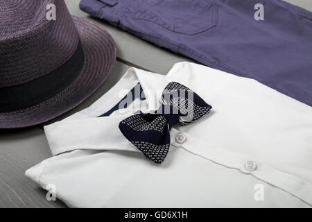 Men's outfit on wooden background. Kids fashion clothes. Grey fedora, navy pant, white shirt, balck bow tie for - Stock Photo