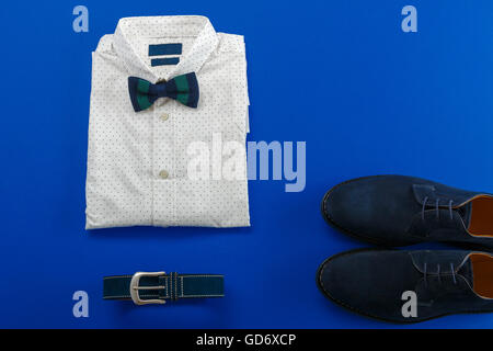 Mens wedding accessory. Mens outfits, white polka-dot shirt with with bow tie, blue belt and shoes on brown background - Stock Photo