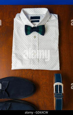 Top view of gentlemanly set. Mens outfits, white polka-dot shirt with with bow tie, blue belt and shoes on brown - Stock Photo