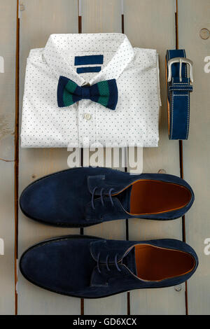 Top view of gentlemanly set. Mens outfits, white polka-dot shirt with with bow tie, blue belt and shoes on grey - Stock Photo