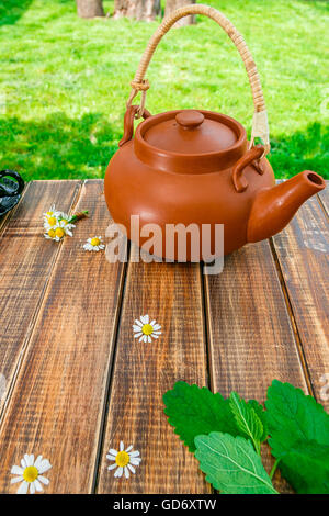 Brown teapoton on wooden with mint and chamomile table in garden and on nature background. Tea concept. Closeup. - Stock Photo