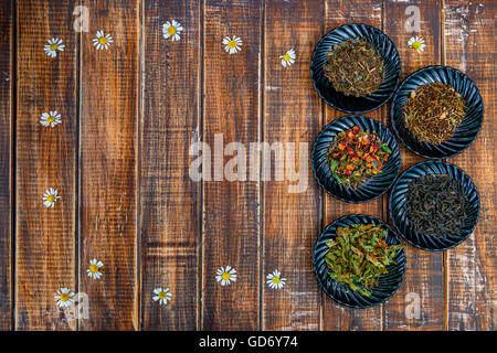 Different kinds of tea on plates on wooden background with flowers of chamomile . Assortment of dry tea. Tea concept. - Stock Photo