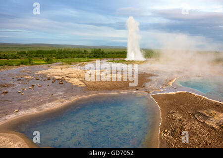 Strokkur (churn) fountain geyser in the geothermal area beside the Hvítá River. Haukadalur, Geysir - Iceland - Stock Photo