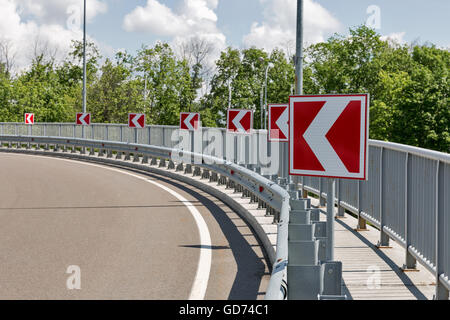 white arrows on red road signs, indicating a protracted left turn - Stock Photo