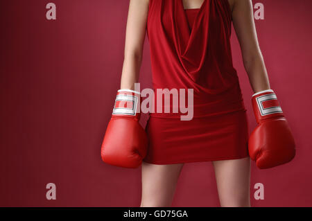 Young woman in red dress wearing boxing gloves - Stock Photo