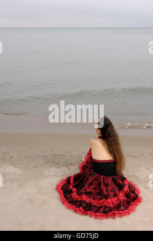 Young woman in red dress sitting alone at the water looking at the horizon - Stock Photo