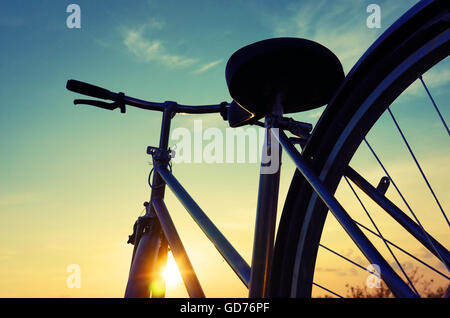Beautiful close up scene of bicycle at sunset, sun on blue sky with vintage colors, silhouette of bike forward to - Stock Photo