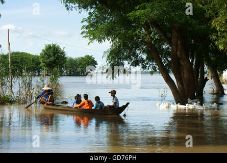 Group of child sitting on row boat, man rowing on river - Stock Photo