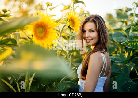 Beautiful happy woman surrounded by sunflowers - Stock Photo