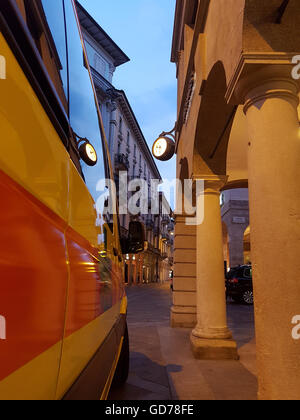 Reflections of Lugano old city center into the side window of an ambulance at night - Stock Photo