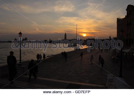 Dusk against the background of the Campanile tower and Basilica of St Marks square.  Grand canal. Foreground silhouetted - Stock Photo