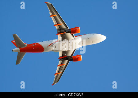 AMSTERDAM, THE NETHERLANDS - FEBRUARY 18, 2015 Bottom of an easyjet plane illuminated by the light of the sun with - Stock Photo