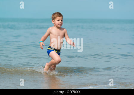 little boy child running through the sea at the beach in the waves in shorts  the joy of life on holiday - Stock Photo