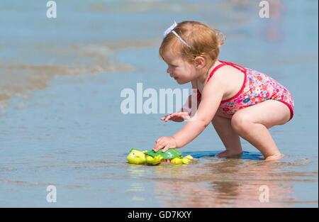 little baby girl on the beach in the sea she's wearing an adorable flower swimsuit looking in the distance discovering - Stock Photo