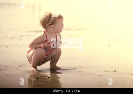 little baby girl on the beach in the sea she's wearing an adorable flower swimsuit - Stock Photo
