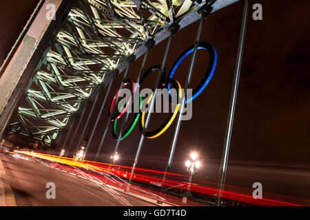 The Olympic Rings hang on the Tyne Bridge in Newcastle during the London Olympics 2012. They are lite up at night - Stock Photo
