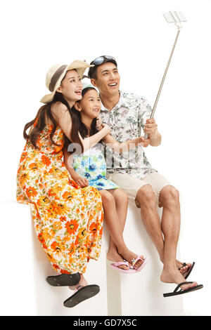 The happiness of a family of three with mobile phone self timer - Stock Photo