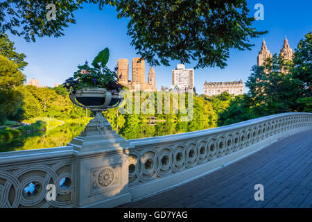Bow Bridge in Central Park, New York City, with Upper West Side residential buildings visible in the distance - Stock Photo