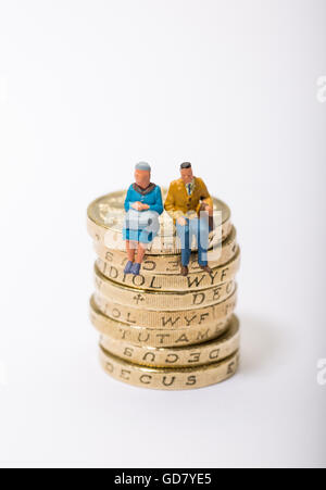 Concept image of two pensioners sat on a pile of pound coins - Stock Photo