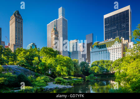 The Pond in Central Park, New York City, with midtown buildings visible in the distance - Stock Photo