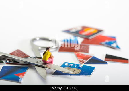 Credit Card dept concept image of a female figure sat with a cut up credit card and a pair of scissors - Stock Photo