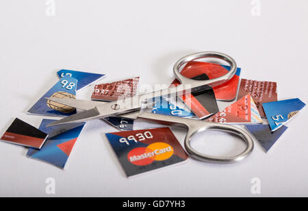 Credit Card dept concept image of a cut up credit card and a pair of scissors - Stock Photo