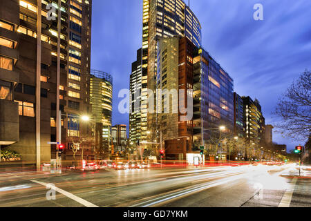 Busy city streets traffic in Sydney at intersection of Elizabeth street with illuminated office buildings at rush - Stock Photo